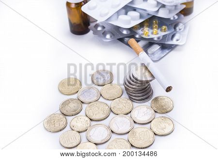 Cigarette on the euro coins with drugs pills and tablets