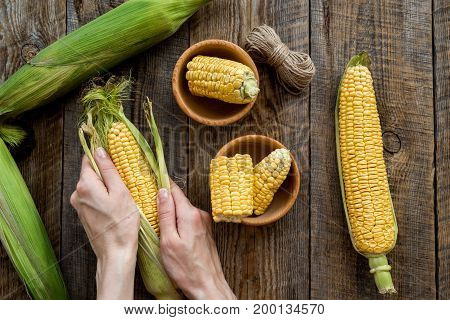 Woman's hands clean corn cob. Black stone background top view.