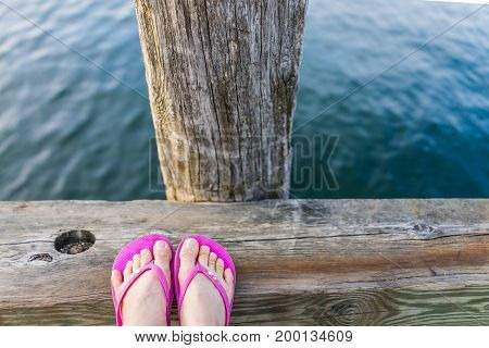 Woman's Feet With Pink Flip-flop Sandal Shoes By Ocean On Wooden Dock Railing Closeup