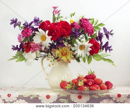 Garden flowers in a white jug and strawberries on the table with a retro tablecloth. Still life with bouquet and berries on a light background.