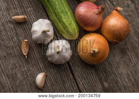 Garlic, Onion, Cucumber, Potatoes And Tomato On An Old Table