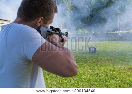 A Man Shoots A Target From A Pneumatic Gun. Rear View Of A Man