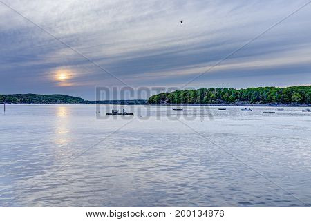 Sunset sun path in Bar Harbor Maine village with empty boats in water