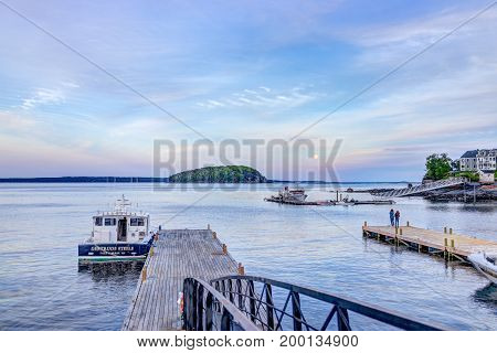 Bar Harbor USA - June 8 2017: View of dock and boat in downtown village in summer during sunset twilight with full moon rising