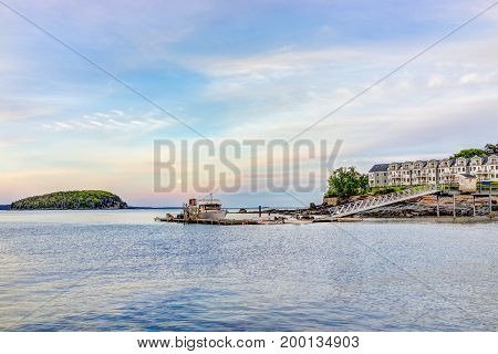 Bar Harbor USA - June 8 2017: View of dock and hotel in downtown village in summer during sunset twilight with full moon rising