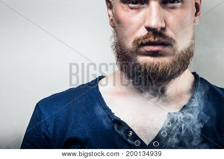 Portrait Of Focused Adult Man With Beard On His Face In Cigarette Smoke. Bad Habit Concept