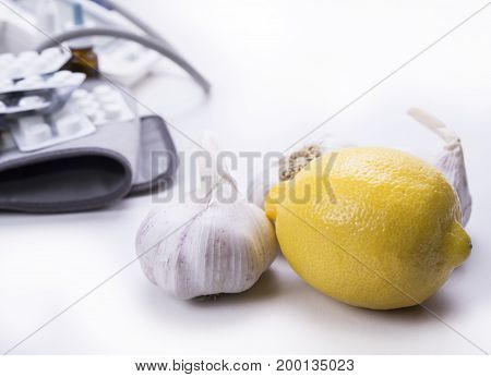 Closeup of garlic and lemon versus drugs and pills