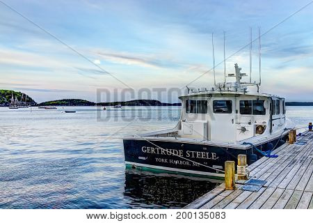 Bar Harbor USA - June 8 2017: View of dock in downtown village in summer during sunset twilight with anchored boat