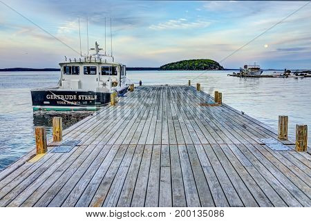 Bar Harbor USA - June 8 2017: View of dock in downtown village in summer during sunset twilight with full moon rising