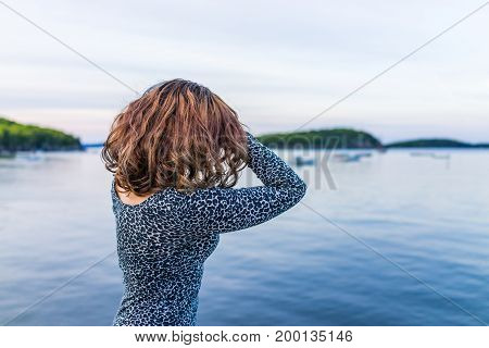 Young Woman With Hands On Head Underneath Hair Overlooking Bar Harbor, Maine Bay