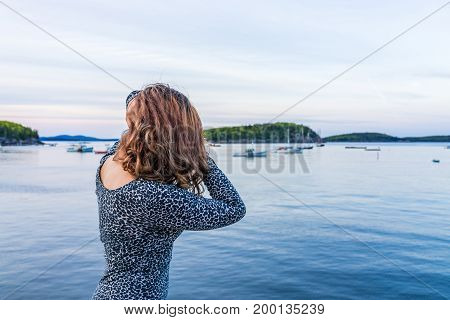 Portrait Of Back Of Young Woman Touching Hair On Edge Of Dock In Bar Harbor, Maine At Sunset
