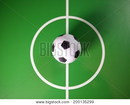 Toy soccerball in a midfield in the center of the green field