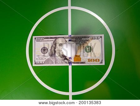 RUSSIA - AUGUST 12 2015: Toy soccer ball in a midfield in the center of the green field and the banknote in hundred dollars