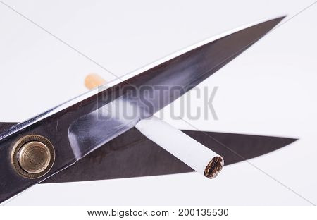 Cut cigarette with scissers and stop smoking to save your health and save money