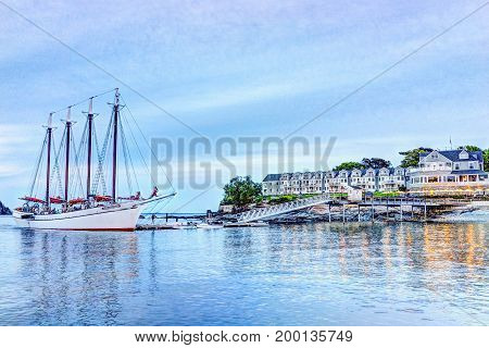 Bar Harbor USA - June 8 2017: View of dock and hotel in downtown village in summer during sunset twilight with reflection of yellow illuminated lights and Margaret Todd windjammer large sailboat