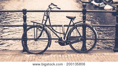 Old bicycle locked on a bridge over water canal, Amsterdam, Netherlands.