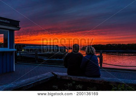 Bar Harbor USA - June 8 2017: Couple sitting in downtown village in summer during bright red sunset twilight