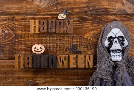 Happy Halloween sign with halloween decorations on a wood background