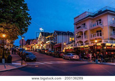 Bar Harbor USA - June 8 2017: People walking sidewalk street by Main road in downtown village during evening night