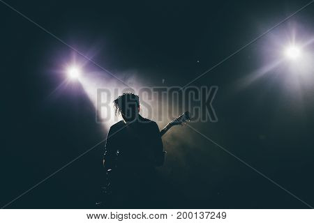 Guitarist silhouette on a stage in a backlights playing rock music