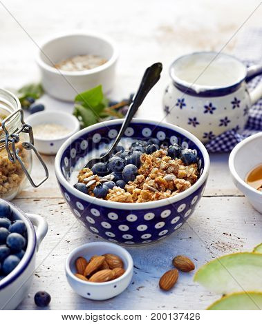 Granola with natural yogurt, fresh blueberries, nuts and honey in a ceramic bowl on a white wooden table. Delicious breakfast or dessert.  Healthy eating concept.
