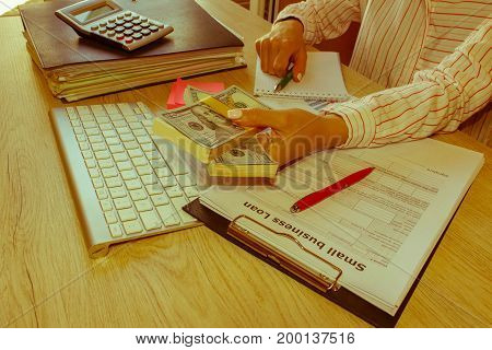 woman holding stack of dollars. Hands close up. Businesswoman Female giving cash money to a person - Retro color
