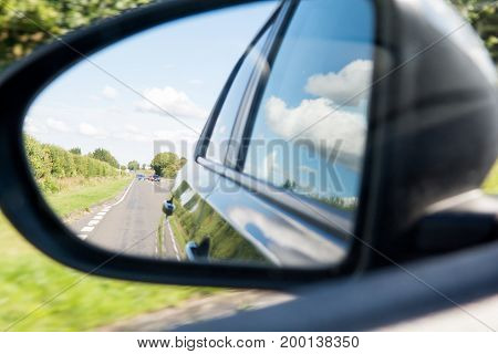 Rear view wing mirror view from passenger side of a moving car