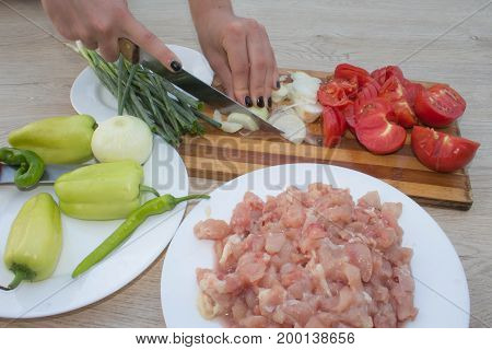Closeup of Human hands cooking food vegetables salad in kitchen. Preparing fresh meal in the kitchen