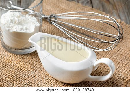 Bechamel white sauce in gravy boat on a wooden background