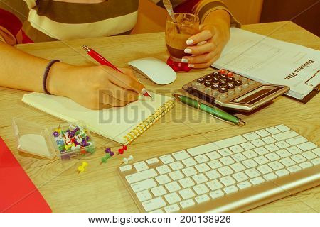 Young woman working in office sitting at desk using computer. Business woman working at the office - Retro color