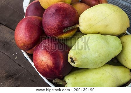 Summer fruit in a fruit basket, pear, apple and nectarine... web design according pears and nectarines photos