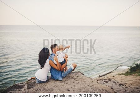 A Young Family Of Three, Mom, Dad And Daughter Spend One Year On A High Cliff Looking At The Sea In