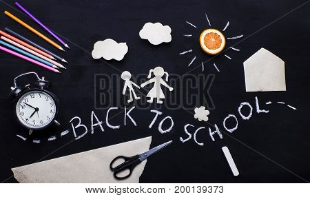 Back to school background with the child going to school. Children's creativity. Application on a blackboard. Pencils scissors and alarm clock on the table. View from above