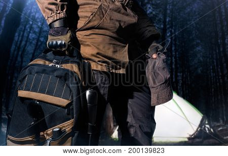 Man in storm jacket and tactical military gloves holding a backpack with travel gear on lightened tent in dark woods background.