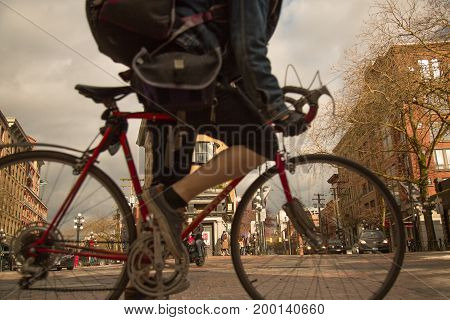 Golden hours historical tourist  district downtown Vancouver Canada man riding bicycle close up