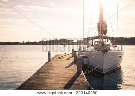 Sailing yacht moored to the pier at sunset, a weekend for lovers of the sea