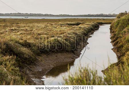 Little fishing boat working along Piedras river marshlands El Rompido Huelva Spain