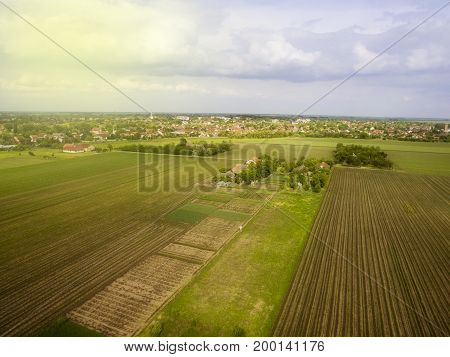 Late afternoon fying above agricultural fields near small town