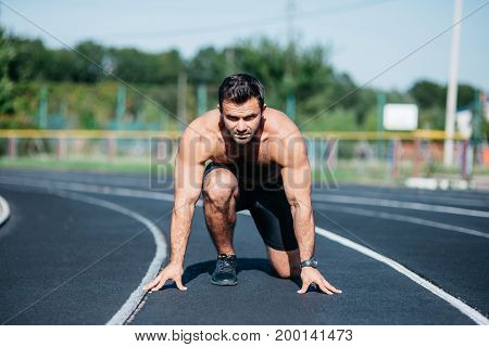 Portrait of the young muscular and butal athlete at the start of the treadmill at the stadium