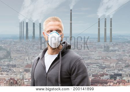 A Man Wearing Pollution Mask Against Smoke Emitting From Factory Chimneys