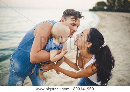 A Young, Beautiful Family Of Three. Mom, Dad And Daughter In The Arms Of My Father Play, Rejoice, Sm