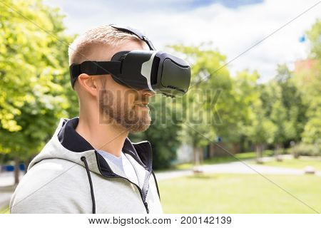 Attractive Bearded Man Enjoying Virtual Reality Glasses In Park