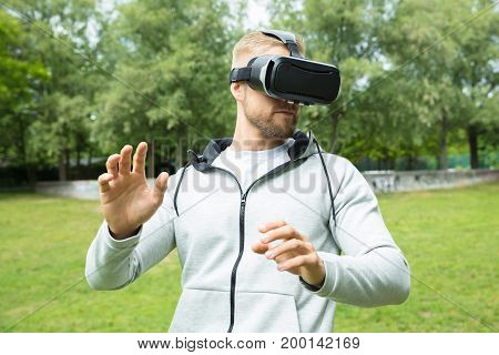 Close-up Of A Man Touching Something Using Virtual Reality Headset Glasses In The Park