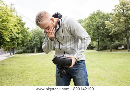 Young Man With Nausea Holding Virtual Reality Headset In The Park