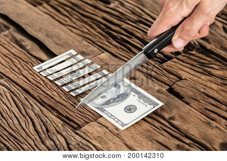 Close-up Of Hand Cutting The 100 Dollar Note With Sharp Knife On Wooden Table