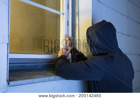 Close-up Of Robber In Hood Using The Red Crowbar To Open The Glass Window