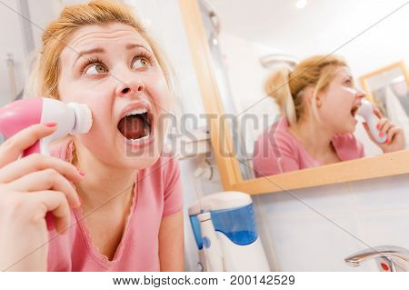 Shocked Woman Using Facial Cleansing Brush