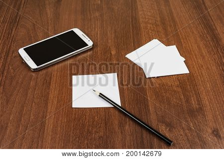 On the surface of the table is a smartphone notes and a pencil
