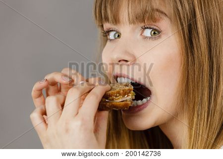 Young woman eating sandwich taking bite with wide open mouth. Food calories dieting concept. Studio shot on grey background profile view.
