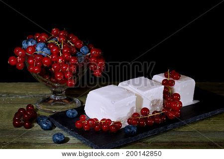 Ice cream with red currant berries. Vase with berries and cream ice cream on an old wooden table. Black background.